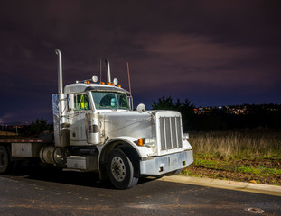 Big rig day cab semi truck with flat bed semi trailer standing on the parking lot in dark night time