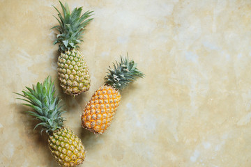 Pineapple on Stone Table Background Top Down View. Summer Exotic Fruit on Retro Tabletop Surface Copy Space. Healthy Ripe Tasty Whole Ananas on Rustic Yellow Texture Backdrop Overhead Closeup