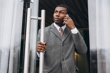 Handsome young african american businessman in classic grey suit holding a smartphone and smiling while leaving the office building