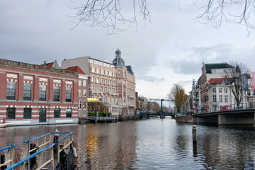 View of the south of canal with Halvemaansbrug bridge in Amsterdam, Netherlands.