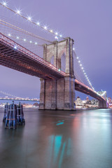 View on Brooklyn bridge at night from east river at night with long exposure