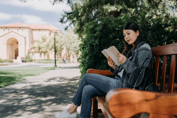 asian female college student sitting on wood bench reading novel book relaxing under tree shadows on sunny day outdoor. young girl studying abroad join short term summer tour program in usa stanford.