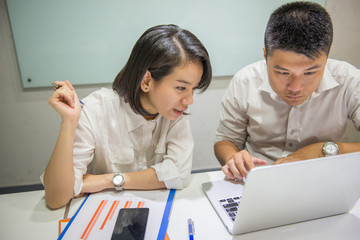 Two Asian office employees working in a team