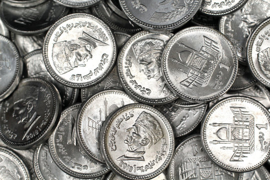 A close up image of a pile of silver Pakistani one rupee silver coins