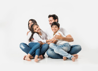 Playful Indian/asian family sitting isolated over white background. selective focus