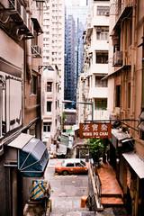 Red Hong Kong taxi cab passes the narrow streets amid tall towers and skyscrapers of Central Hong Kong.