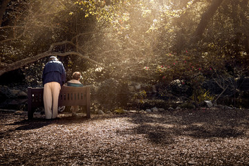 Senior couple sitting on a bench in an outdoor park in front of a pond.  The retired husband and wife are depicting elderly relationship and lifestyle.