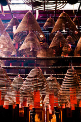 Large pyramid shaped incense coils smoking at a Chinese temple. The donors of the incense are written on red tags in Chinese characters.