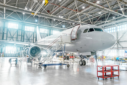 Aircraft under maintenance, checking mechanical systems for flight operations. Plane in the hangar