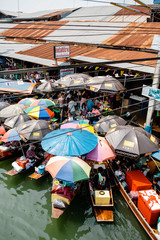 Thai vendors paddle small wooden boats, shaded with brightly colored umbrellas, to the side of the river to sell their food and snacks at a floating market.