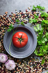 Fresh tomato in a bowl surrounded by legumes