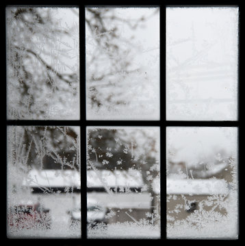 Crystal snowflakes shapes blur winter view through silhouette window