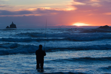 A fisherman in the surf as Tillamook lighthouse looks on