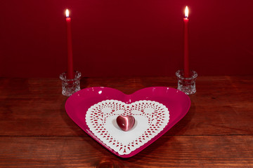 Pink heart shapped plate with dollie and gemstone, two red candles in crystal holoders on wooden table.