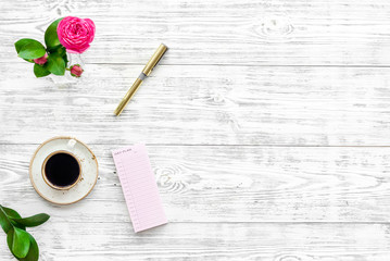 Home work desk, feminine workplace. Notebook and stationery near pink flowers and coffee on white wooden background top view space for text