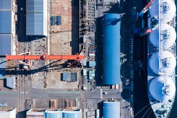 倉庫のある工業地帯の港に停泊するタンカー船の空撮。
