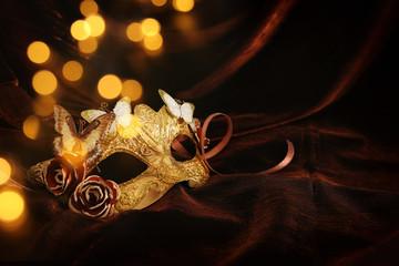 Photo of elegant and delicate gold venetian mask over dark silk background.