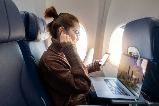 Beautiful Asian woman is working with laptop in airplane