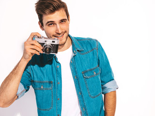 Portrait of handsome smiling man wearing summer hipster jeans clothes. Model male taking picture on old vintage photo camera. Isolated on white