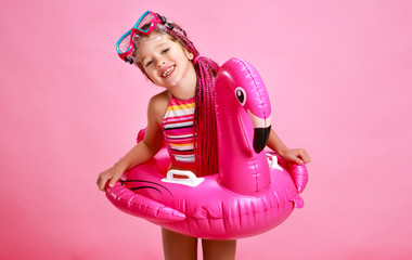 happy child girl in swimsuit with swimming ring flamingo on colored pink background