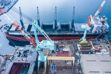 工業地域の港でメンテナンスをされている大型船。