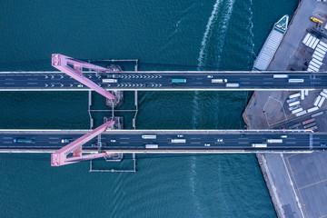 海の上に架かる橋の先にはコンテナ船などがある