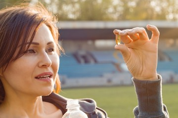 Outdoor portrait of mature woman taking vitamin E capsule pill of cod liver oil, at stadium. Sport, healthy lifestyle and nutrition, healthcare concept