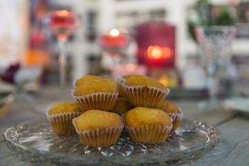 Muffins auf der Kuchentafel mit Kerzenlicht im Hintergrund
