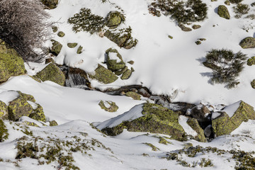 rocks covered with ice, water and snow in the mountains of Madrid
