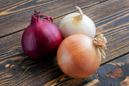 Red, white and yellow onions on wooden background.