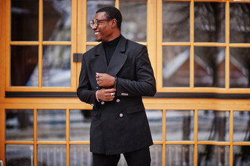 Stylish african american gentleman in elegant black jacket. Rich fashionable afro man against window.