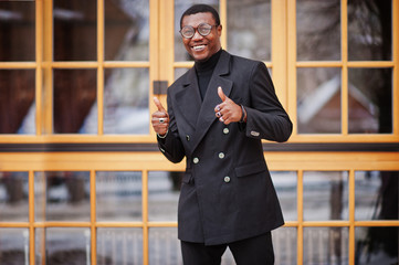Stylish african american gentleman in elegant black jacket. Rich fashionable afro man against window show thumb up.