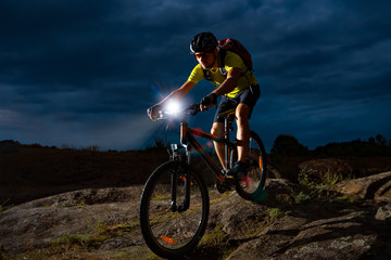 Cyclist Riding the Mountain Bike on Rocky Trail at Night. Extreme Sport and Enduro Biking Concept. Fototapete