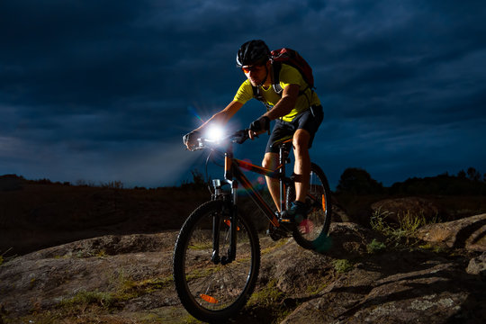 Cyclist Riding the Mountain Bike on Rocky Trail at Night. Extreme Sport and Enduro Biking Concept.