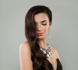 Smiling woman brunette with makeup, long brown hair and diamond necklace and earrings, fashion portrait