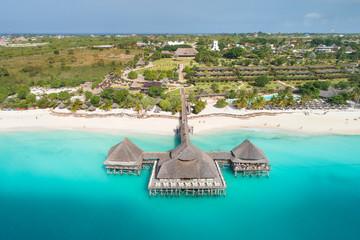 Obraz wooden restaurant on pier in emerald water on Zanzibar island - fototapety do salonu