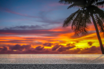 Palm tree with burning sunset in dramatic sky. Empty table top for product display montage background.