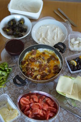 Traditional Turkish Country Breakfast with Turkish sausage and egg, sliced tomato, fresh and organic green pepper, butter, black olives, cheese, jam, milk cream and tea