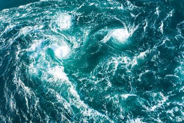 白い波が無数の渦を巻いている海の風景