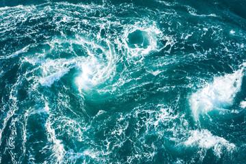 白い波が無数の渦を作り出している海の風景