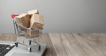 Delivery of the order from the online store. Online shopping. Boxes with goods in the shopping basket on the table with laptop. Copy space for text.