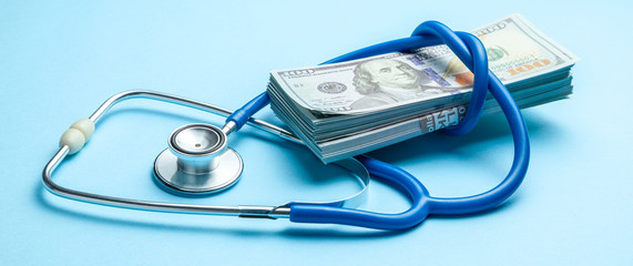 Stack of cash dollars and stethoscope on blue background. The concept of medical strechevka or expensive medicine, doctors salary