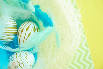 colorful background for easter, eggs in a nest with blue feathers