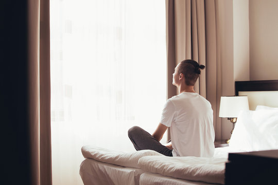 Cute young guy woke up and meditates on his bed in the lotus position looking out the window of his bedroom. Concept of cheerfulness and good mood for the whole day