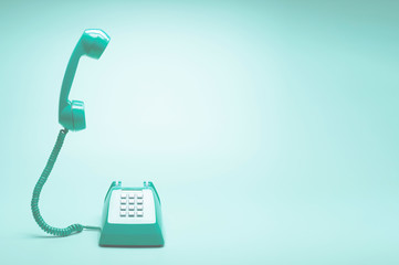 Retro green telephone on teal green background