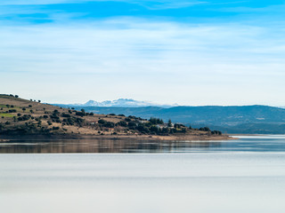 Landscape of a reservoir and mountains in a day with fog and clouds and birds swimming and flying in in La Maya Reservoir (Salamanca)