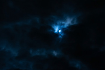 The white moon in the dark blue clouds of night.