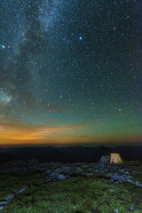 The starry sky in the mountains witha galaxy is a Milky way on the background of a tourist tent.