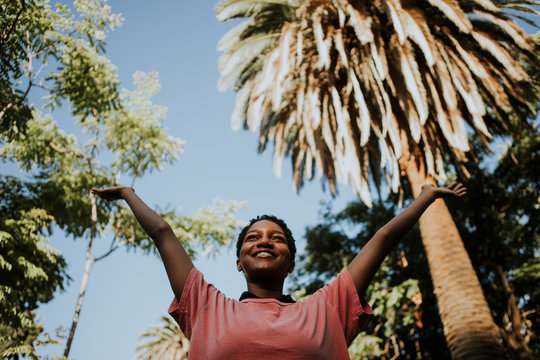 Happy woman feeling free in the park