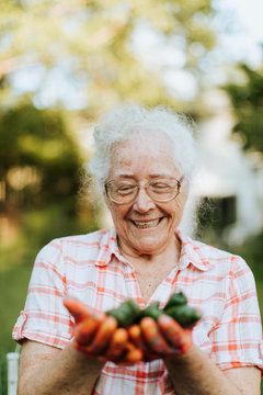 Senior woman holding organic jalapeno peppers from her own garden